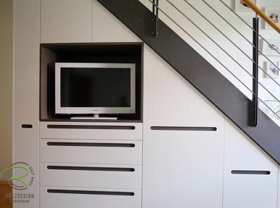 Treppenunterschrank nach Maß mit weiß & anthrazit lackierter Front, mit indirekt beleuchteter Fernsehernische, flächenbündige Griffmulde anthrazit lackiert, mit Schubalden, Platz für Bügelbrett, Dampfbügelstation, Staubsauger