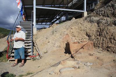 Prof. Licheli vor dem großen Flugdach, das die Grabungen schützt. Rechts im Bild einer der zahlreichen Feueraltäre bzw Kultöfen zum Backen von heiligem Brot.