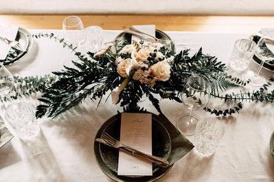 Eine Hochzeitstafel ist mit Geschirr, Blumen und Kerzen geschmückt.
