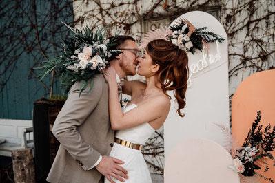 Ein Brautpaar hält einen Blumenstrauß in die Kamera.
