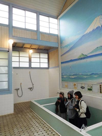 子宝湯の湯舟で少女三人がカメラを構えているシュールな図。