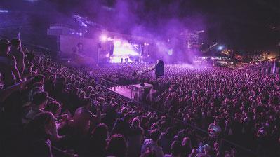 Open Air Konzert mit vielen Menschen und violettem Licht