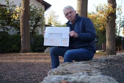 Bruno Matzke vom Hüder Dorfverein sitzt auf einer Steinmauer auf dem Hüder Dorfplatz und präsentiert eine Skizze der geplanten Bühne.