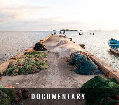 Cotton and nylon fishing nets with red floats lie on a concrete jetty in Carnage while three fishers are located at the end of the jetty