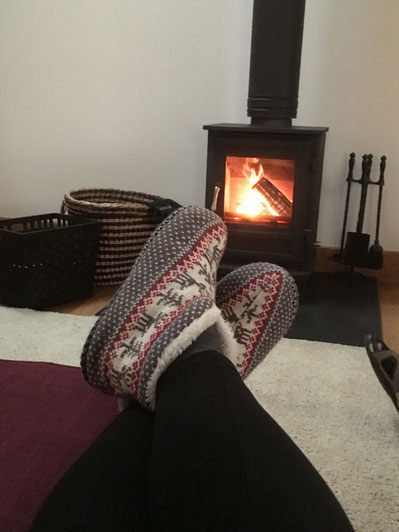 Cozy slippers and a warm fire at Baillie Scott Cottage