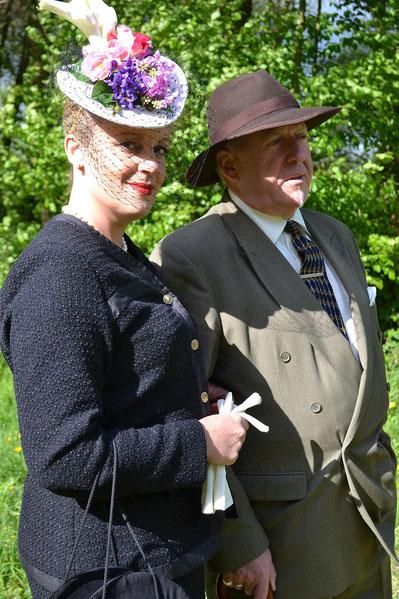 Déatils des chapeaux (bibi et borsalino) et des vêtements (tailleur haute couture femme, costume homme à croisé double)