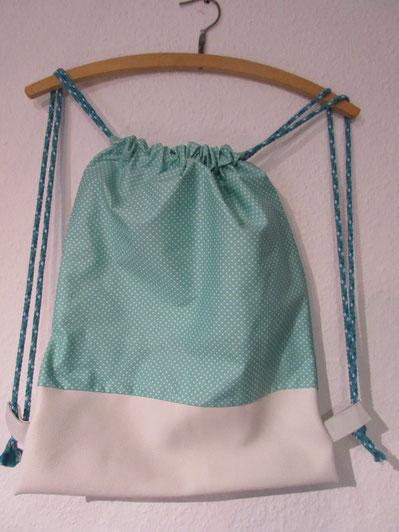Sportbeutel aus beschichteter Baumwolle in türkis mit weißen Punkten. Das untere Teil ist aus Kunstleder. Der Sportbeutel besitzt auch ein Innenfutter.