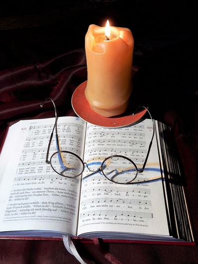 Aufgeschlagenes Gotteslob mit Brille und Kerze