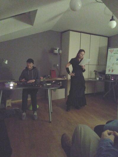 Hier sieht man eine Frau in schwarzer Kleidung, die einem Publikum etwas vorliest. Links daneben sitzt ein Mann an elektronischen Synthezisern.