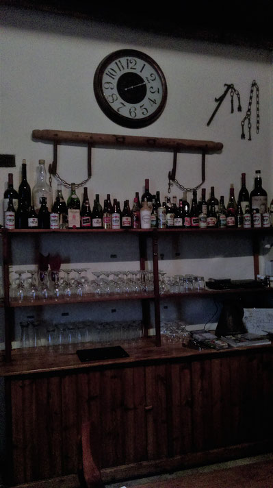 Bar with old bottley of liquor, glasses, red wine, white wine, whiskey, cognac, sherry, a chair in the front. South Africa.