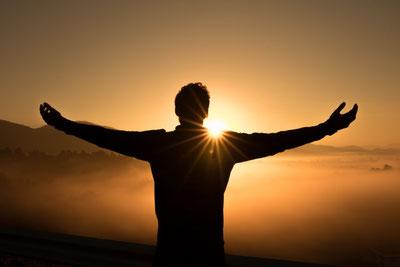 Mann schaut mit ausgestreckten Armen der aufgehenden Sonne entgegen