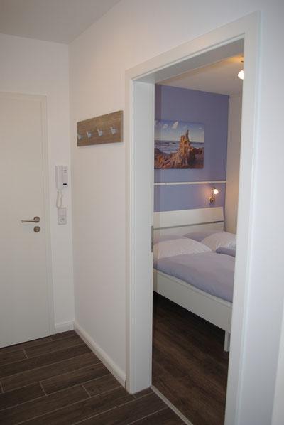 Blick aus dem Flur mit Garderobe und großem Spiegel in das weitere Schlafzimmer