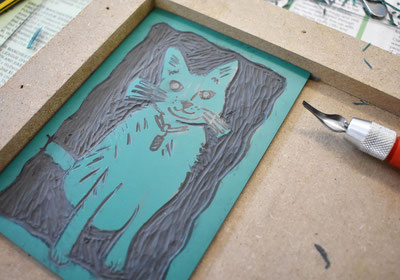 Cutting into a linocut plate at a linocut printmaking workshop