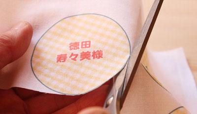 印刷した布をはさみで切る