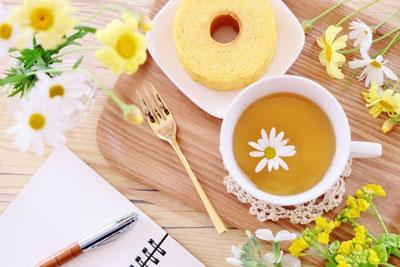 広げられたリングノートとボールペン。トレイに載ったバームクーヘンのお皿とハーブティーのカップ。ガラスの小瓶に活けられたカモミールの花。