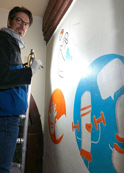 Frank Schulz zeichnet mit Acrylmarker auf eine Wand