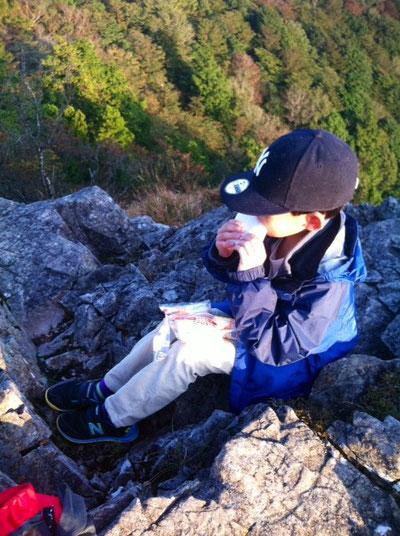 """寒いんで岩陰に隠れ小さくなって""""ランチパックを食べる""""の図。"""