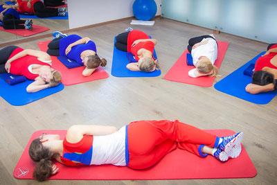 Eine Gruppe von Schwangeren machen nach dem Sport noch Entspannungsübungen. Sie liegen auf dem Boden auf einer Matte. Hand auf dem Bauch.