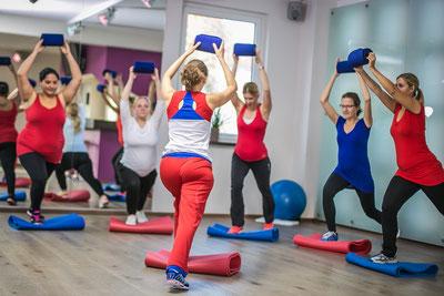 Eine Gruppe schwangere Frauen und eine Trainerin machen zusammen Sport. Sie machen einen Schritt nach vorne und halten ein leichtes Gewicht dabei in die Luft.