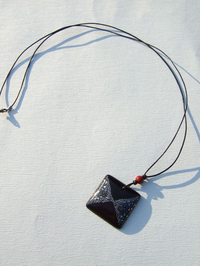 水牛の黒紐に赤うるしの玉。