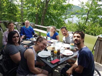 Membres et bénévoles accompagnateurs assis à table sur le balcon d'un chalet avec vue sur le lac et la forêt.