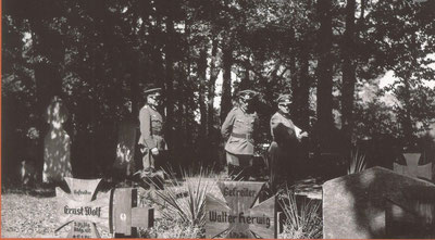 "General Otto von Stülnagel, who survived WW1, pauses by the graves of German P.O.W's who did not return. The Oak crosses of the early WW2 dead were later replaced with smaller metal ""Iron Crosses"""