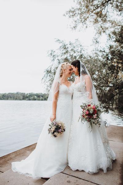 Regenbogenhochzeit mit zwei Bräuten in weißen Brautkleidern