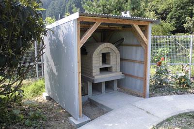 完成した手作りのピザ釜と小屋。