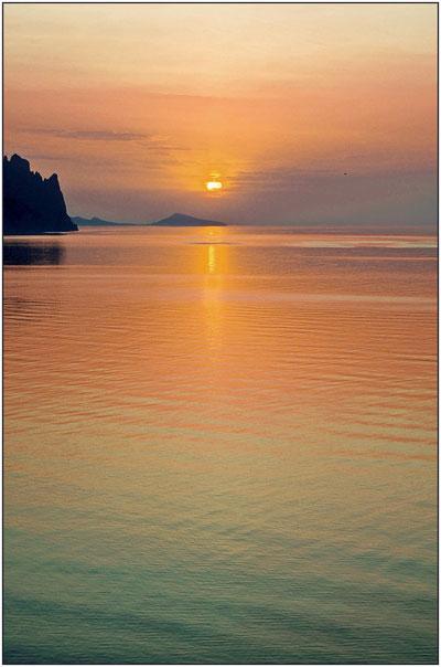 Красивый восход солнца над морем около вулкана Карадаг в Крыму