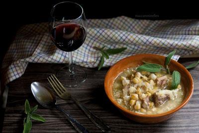 Tavolo con ciotola di zuppa di cieci, un bicchiere con vino, posate.