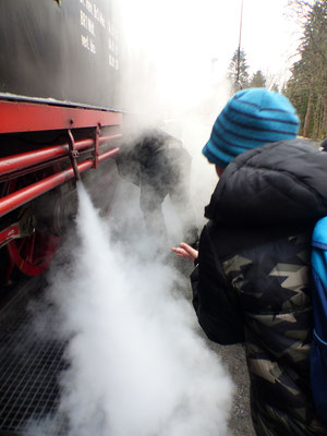 EIn Schüler testet den Wasserdampf an der Lok