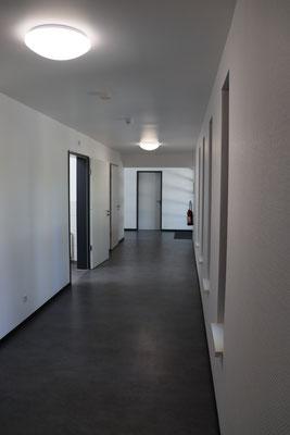"""Der Gang vom """"alten"""" zum """"neuen"""" Eingang. Links das behindertengerechte WC, dahinter die neue Küche, am Ende des Gangs der Technikraum und rechts der SportlerInneneingang."""