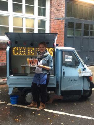 Lilli steht mit einem Tablett mit gefüllten Proseccogläsern vor der mobilen Bar