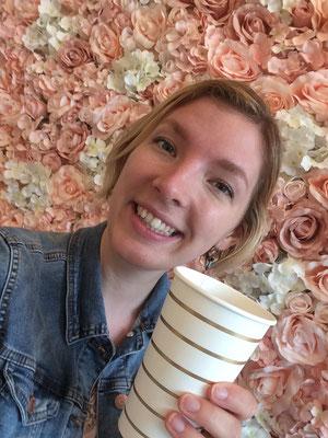 Yvonne mit Secco-Becher vor der Flowerwall