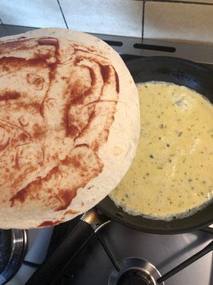 Den bestrichenen Tortillafladen auf das Omlette geben