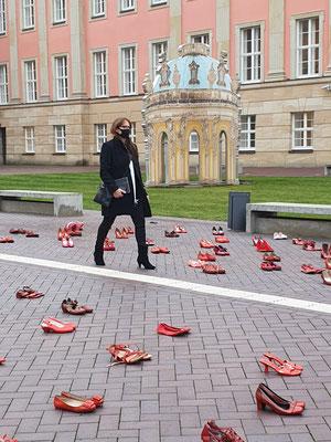 Katrin Lange läuft über den Innenhof des Landtags durch eine Installation von roten Damenschuhen