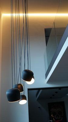 Blick vom Esstisch zum Obergeschoss auf die deckenintegrierte Lichtlinie LEDsREADY von EMS