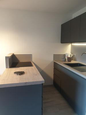 Aménagement appartement de station, cuisine équipée, anthracite, chêne clair, meuble suspendu, ilot de cuisson, plan de travail, les Orres, Hautes Alpes