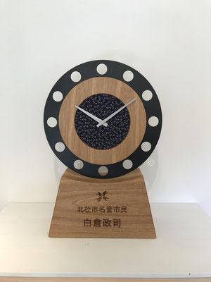 甲州印伝クロックを置時計としてまとめた記念品。八ヶ岳のライフスタイルブランドであるfeeLife YATSUGATAKEの作品。八ヶ岳の家具工房ZEROSSOの創作家具。