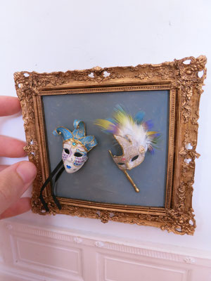 Frame with two venetian masks: music and feathers