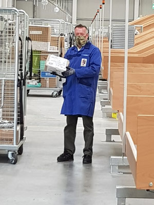 FInsp MÖRTL beim Einräumen der Pakete von der Rutsche in den Rollcontainer