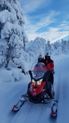 Snowmobile tour through the snowy forests