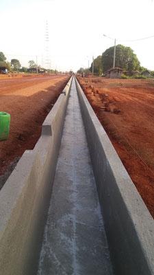 Caniveau U réalisée avec un coffrage glissant, les passages d'eau sont réalisés dans le béton frais manuellement - Chantier Colas/Razel en Cote d'Ivoire