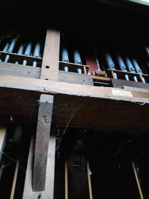 Derrière l'orgue, une vue du sommier soutenant les tuyaux avec les tiresttes en dessous.