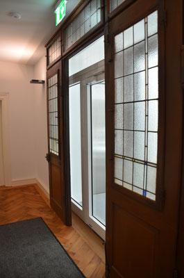 erneuter Einbau der alten Geschosseingangstüren hinter der neuen notwendigen Brandschutztüre