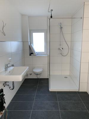 Moderne Wand- und Bodenfliesen sowie den Einbau einer fast ebenerdigen Dusche verschönern das Badezimmer.