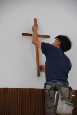2020年5月19日(火)昼前 大工さんが事前の準備をそうとう慎重になさって、一気に十字架の位置を高く白壁に移動して頂く工事を40分程の時間をかけてなさいました。仕事ぶりを全部みていましたが、見事です。