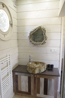 Das Badezimmer mit dem Waschbecken aus versteinertes Holz