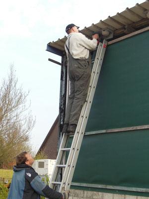 Gerold und Jan hängen Nisthilfen an einem Pferdestall auf