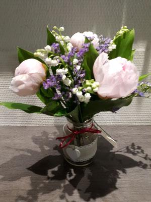 Bouquet de muguet de Bordeaux et lisianthus dans un vase décoré